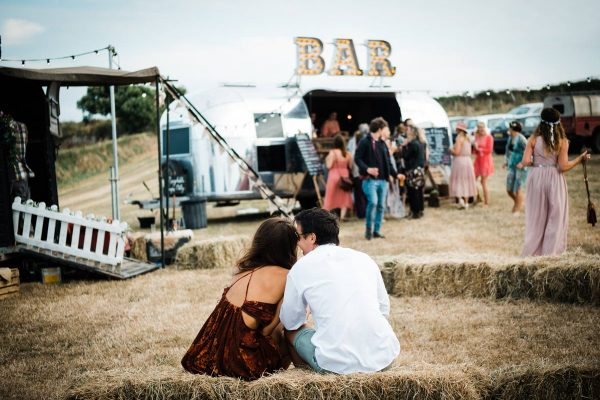 couple-sat-on-hay-bale-at-wedding-cornwall