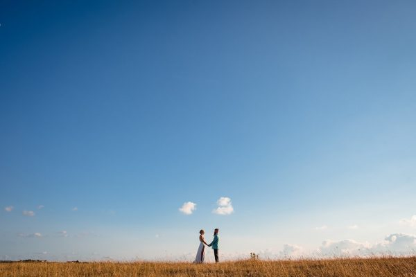 couple-stood-in-field-with-blue-sky